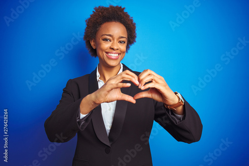 Poster Individuel African american business executive woman over isolated blue background smiling in love showing heart symbol and shape with hands. Romantic concept.