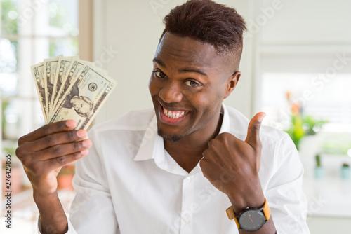 Fényképezés  African american man holding twenty dollars bank notes happy with big smile doin