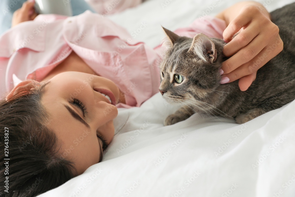Fototapety, obrazy: Young woman with cute cat on bed. Pet and owner