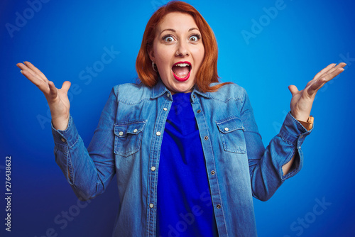 Poster Individuel Young beautiful redhead woman wearing denim shirt standing over blue isolated background celebrating crazy and amazed for success with arms raised and open eyes screaming excited. Winner concept