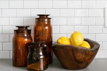 Lemons In Wooden Bowl And Amber Jars On Concrete Kitchen Countertop, White Subway Tile Backsplash