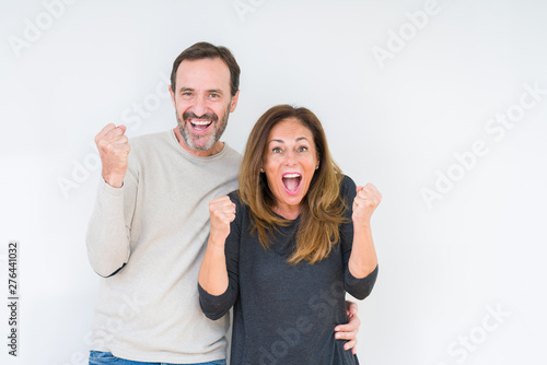 Poster Individuel Beautiful middle age couple in love over isolated background celebrating surprised and amazed for success with arms raised and open eyes. Winner concept.