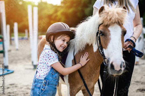 Cute little girl and her older sister enjoying with pony horse outdoors at ranch Tableau sur Toile