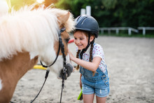 Cute Little Girl Enjoying With Pony Horse Outdoors At Ranch.