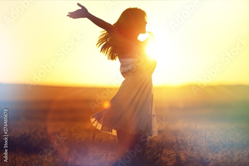 Young woman on field under sunset light Fototapete