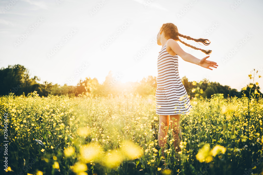 Fototapety, obrazy: A little girl with two pigtails in a rapeseed field at the sunset. Concept of happy summer.