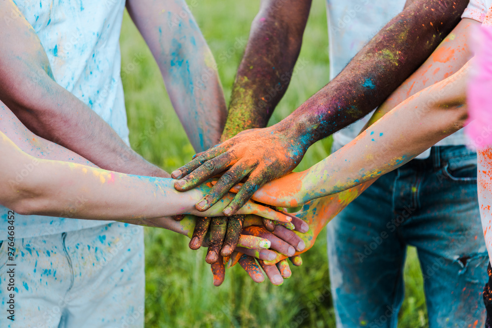 Fototapeta cropped view of multicultural friends with colorful holi paints putting hands together