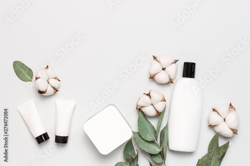 Poster Spa Cosmetics SPA branding mock-up. White cosmetic bottle containers with cotton flowers, eucalyptus twigs on gray background top view flat lay. Natural organic beauty product concept, Minimalism style