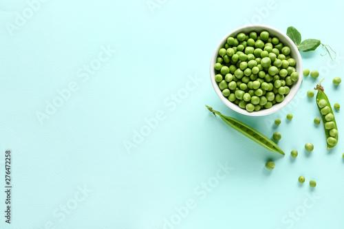 Fototapeta Bowl with tasty fresh peas on color background