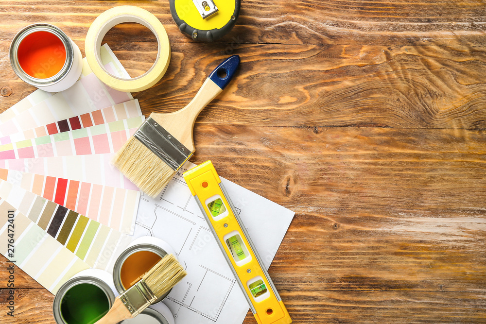 Fotografía Cans of paint with supplies, palette samples and house plan on wooden table
