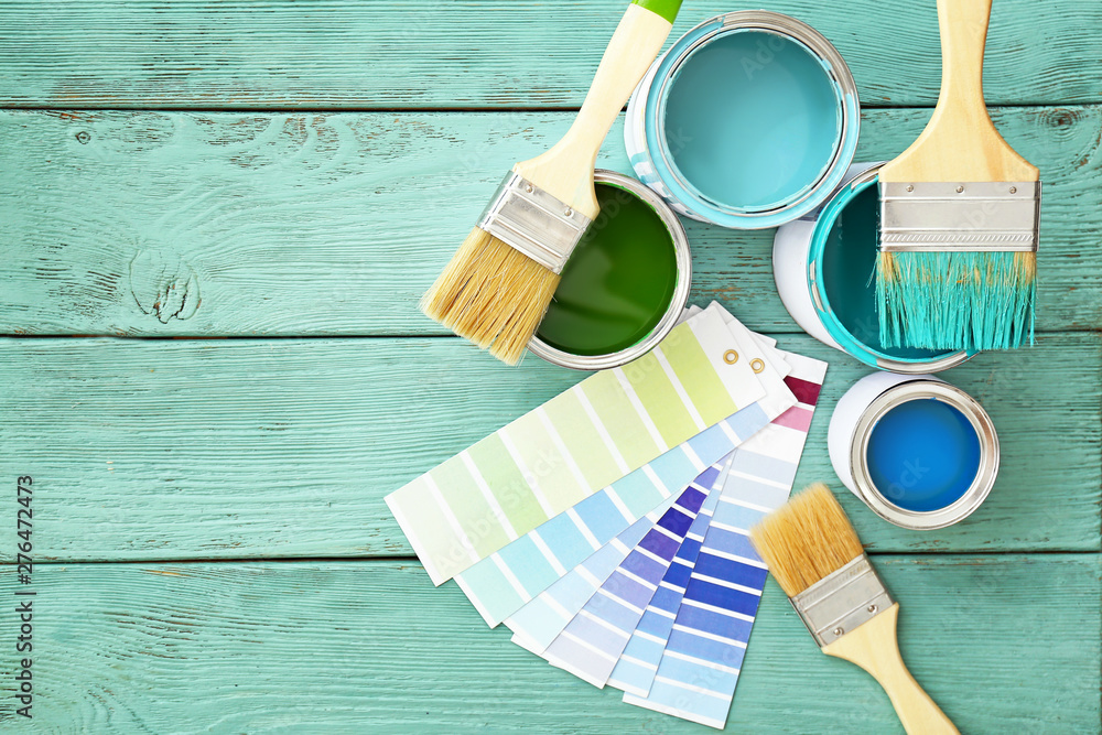 Fototapeta Cans of paint with brushes and palette samples on wooden background