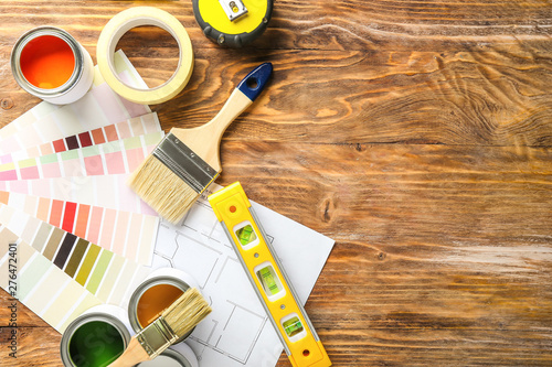 Fotomural Cans of paint with supplies, palette samples and house plan on wooden table