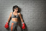 Sporty female boxer near light brick wall