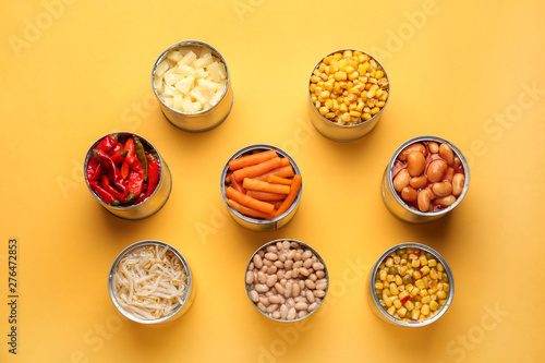 Photo  Tin cans with different food on color background