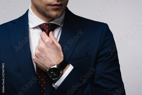 Fotografia partial view of businessman touching tie isolated on grey