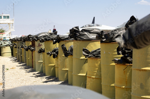 A protective barrier of heavy oil drum barrels on a military base