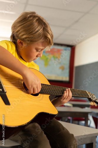 Boy playing guitar in a classroom