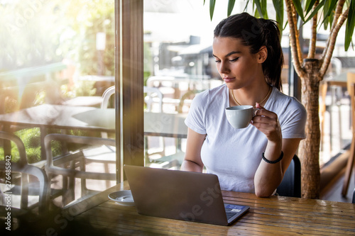 Photo  Young beautiful girl sitting at a table in a cafe by the window, drinking cappuccino coffee