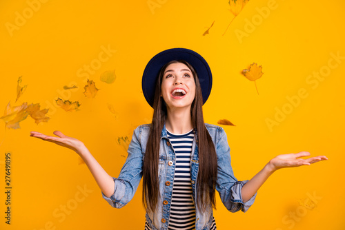 Portrait of her she nice charming winsome attractive lovely optimistic cheerful cheery straight-haired lady throwing leaves having fun time isolated over bright vivid shine yellow background