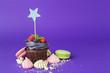 Leinwanddruck Bild - Beautiful cupcake against saturated dark purple background