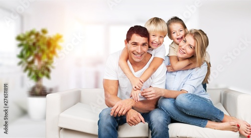 Obraz Young family at home smiling at camera - fototapety do salonu