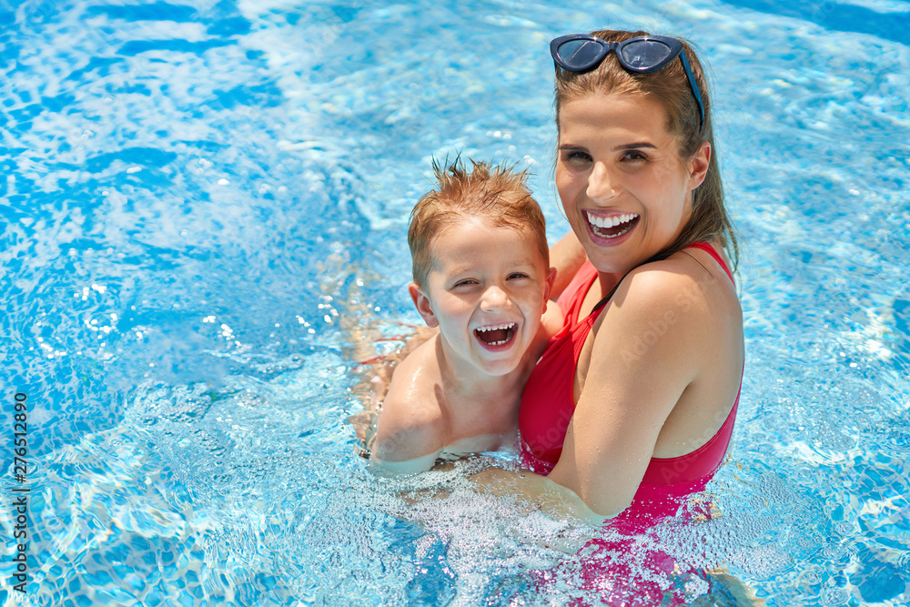 Fototapeta Cute boy with his mother playing in swimming pool during summer