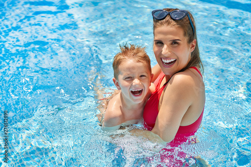 Obraz Cute boy with his mother playing in swimming pool during summer - fototapety do salonu