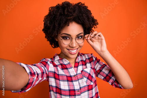 Poster Individuel Photo of funny lady making selfies playful hold hand eyewear wear specs casual checkered shirt isolated orange bright background