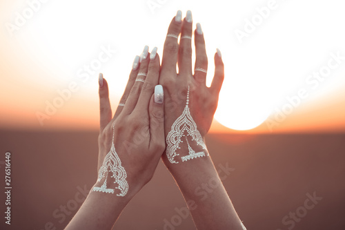 La pose en embrasure Style Boho Boho style white hand tattoo. Bohemian woman carefree at the sunset, outddoor photo.