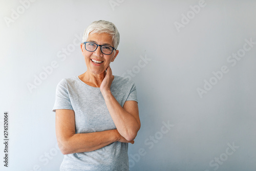 Obraz Close up portrait of a professional business woman smiling. Portrait of cheerful mature woman standing against grey wall. Close up portrait of beautiful older woman smiling and standing by wall - fototapety do salonu