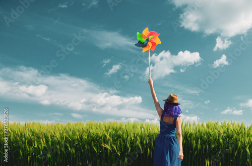 Valokuva purple hair girl with pinwheel at wheat field