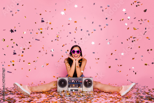 Portrait of her she nice-looking lovely attractive cheerful cheery positive girl sitting on floor having fun time event holiday flying decorative elements isolated over pink pastel background - 276527667