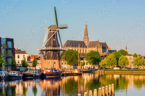 Fotografie, Obraz  Skyline of Haarlem, North Holland, Netherlands, with Windmill De Adriaan from 1779 and 13th Century Saint Bavo Church
