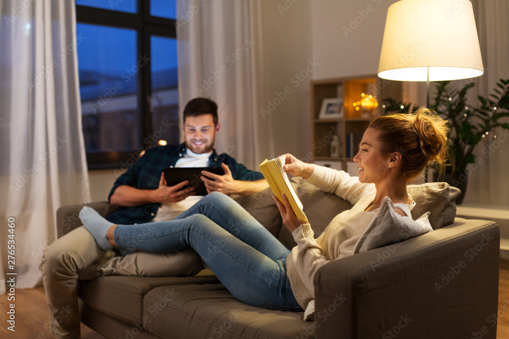 Fototapeta leisure and people concept - happy couple with tablet computer and book at home in evening