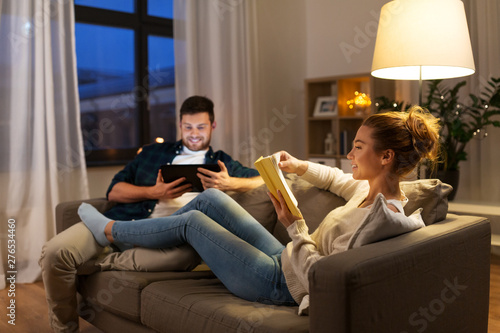 Obraz leisure and people concept - happy couple with tablet computer and book at home in evening - fototapety do salonu