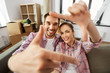 Leinwandbild Motiv moving, repair and real estate concept - smiling couple taking selfie and making hand frame gesture at new home