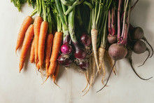 Variety Of Root Garden Vegetables Carrot, Purple Onion, Beetroot, Parsnip With Tops Over White Marble Background. Top View, Space