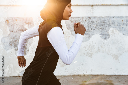 Fotografiet Strong muslim sports fitness woman dressed in hijab and dark clothes running outdoors
