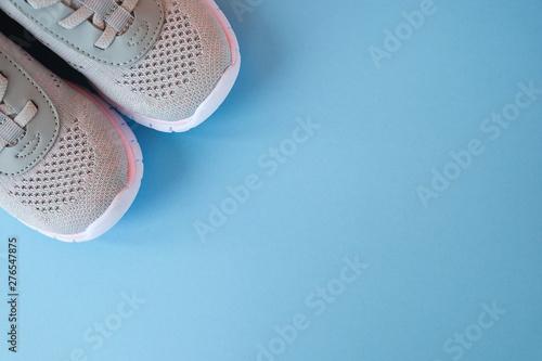 Fototapeta Sport, healthy lifestyle concept. New gray sneakers on pastel blue background. Copy space. Flat lay obraz na płótnie