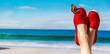 Leinwandbild Motiv Beine mit roten Stoffschuhen vor Strand und Meer