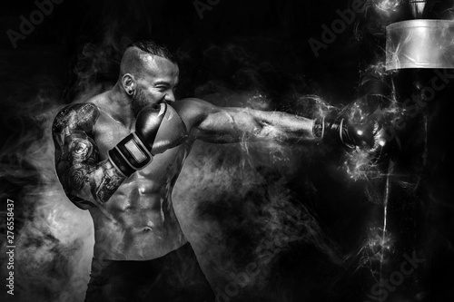 Sportsman man boxer fighting in gloves with boxing punching bag on dark background with smoke. Copy Space. Black and white photo.