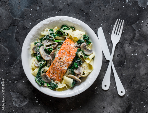 Pappardelle pasta with creamy spinach mushrooms sauce and baked salmon on a dark background, top view Canvas Print