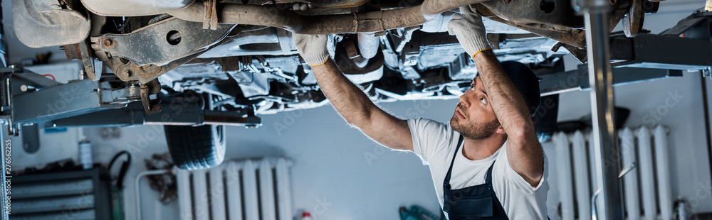 Fototapeta panoramic shot of handsome car mechanic repairing automobile