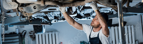 plakat panoramic shot of handsome car mechanic repairing automobile