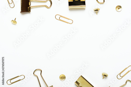 Photo  Golden buttons, paper clips and stationery clips on a white background