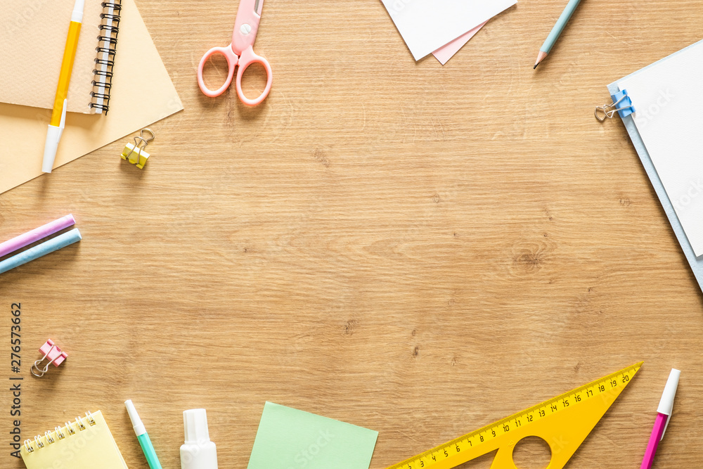 Fototapeta Flat lay school stationery on a wooden background. Back to school concept, creative layout. Top view, overhead.
