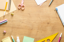 Flat Lay School Stationery On A Wooden Background. Back To School Concept, Creative Layout. Top View, Overhead.