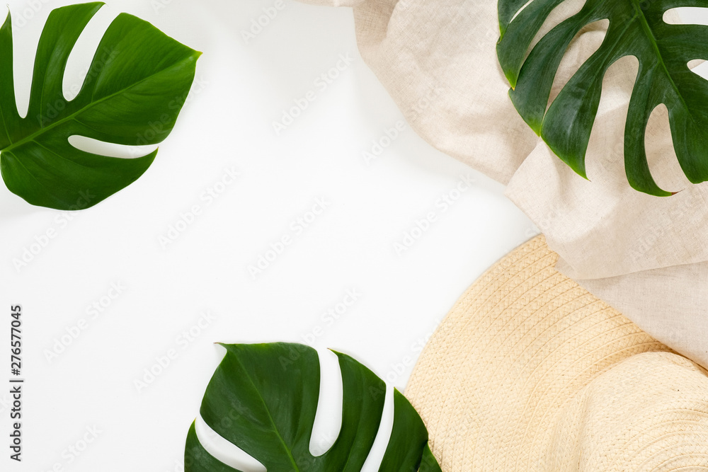 Fototapety, obrazy: Summer vacation concept with tropical monstera leaves and straw hat on white background. Minimal flat lay style composition with copy space. Top view, overhead.