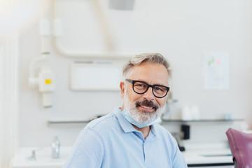 lächelnder Zahnarzt im Behandlungszimmer