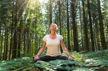 Experience The Forest While Bathing In The Forest (Shinrin Yoku) With All Her Senses. A 50 Year Old Blonde Woman Sits Cross Legged Relaxed. She Fuels The Sun And The Atmosphere Of The Forest.